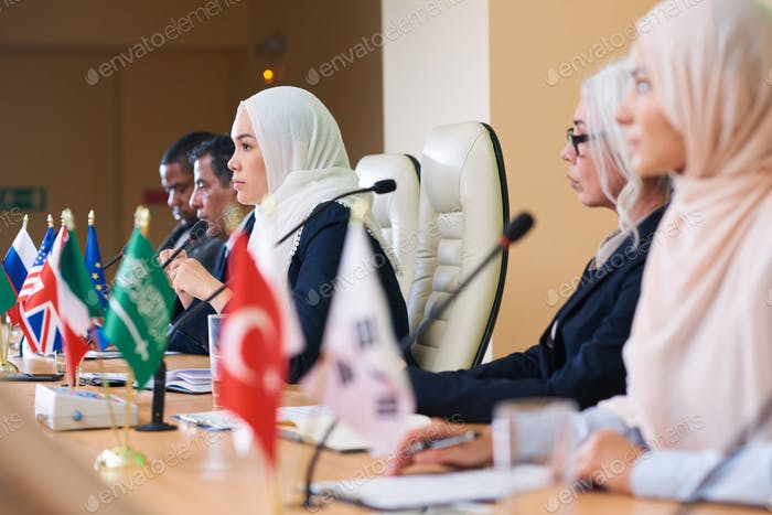 Row of serious intercultural delegates listening attentively