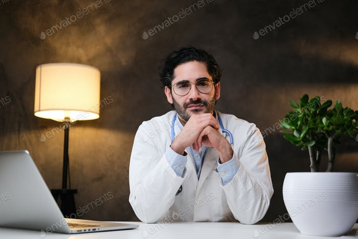 Surgeon sits at table and looking at camear in dark background