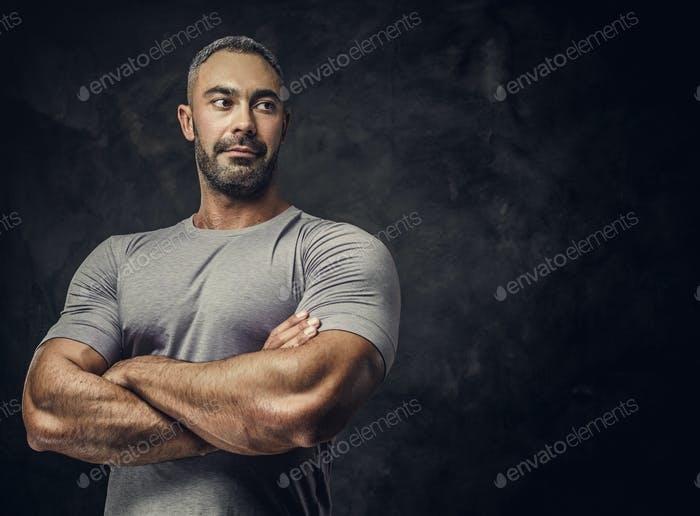 Adult caucasian muscular bodybuilder in a studio