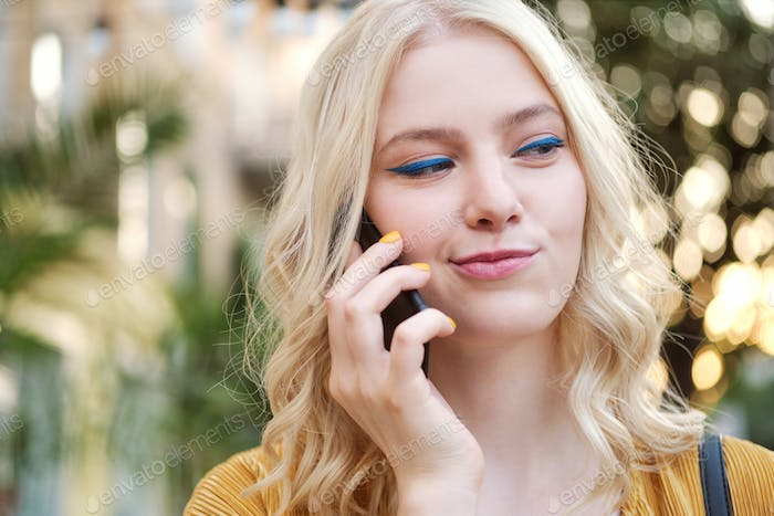 Portrait of beautiful flirty blond girl cunningly looking away talking on cellphone outdoor