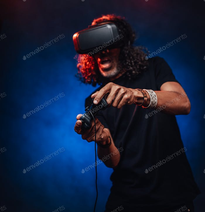 Middle aged hispanic male playing with virtual reality glasses and video game controller