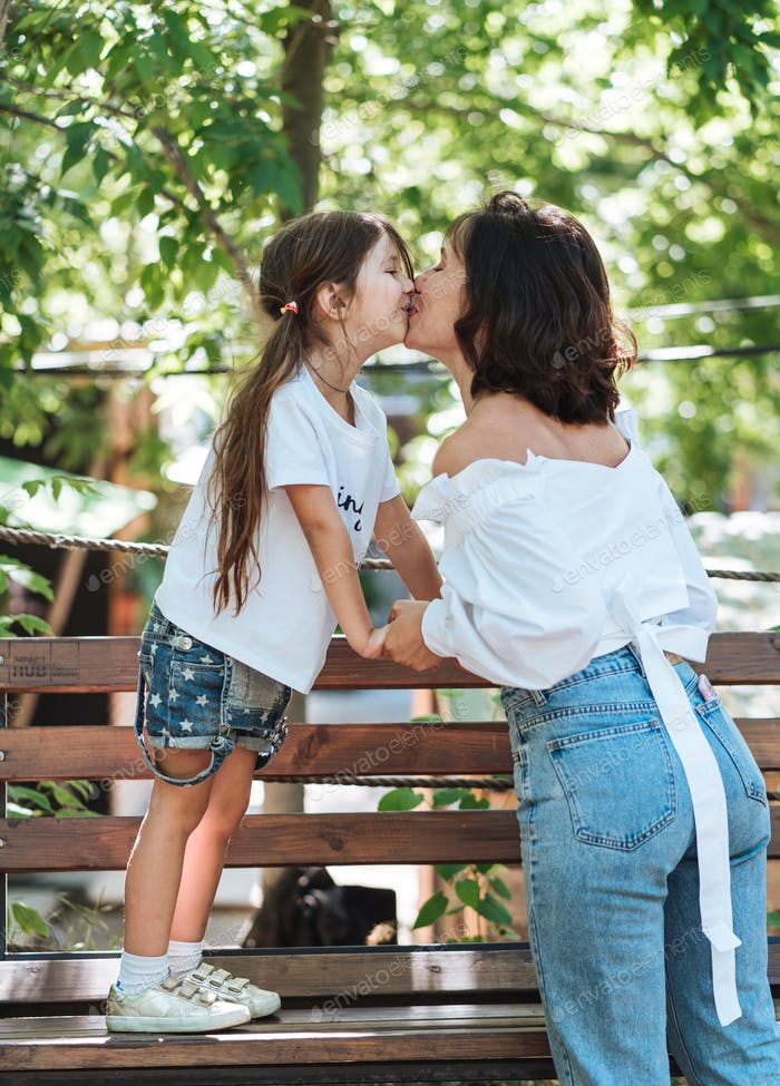 Young mother hugging her little girl in the park