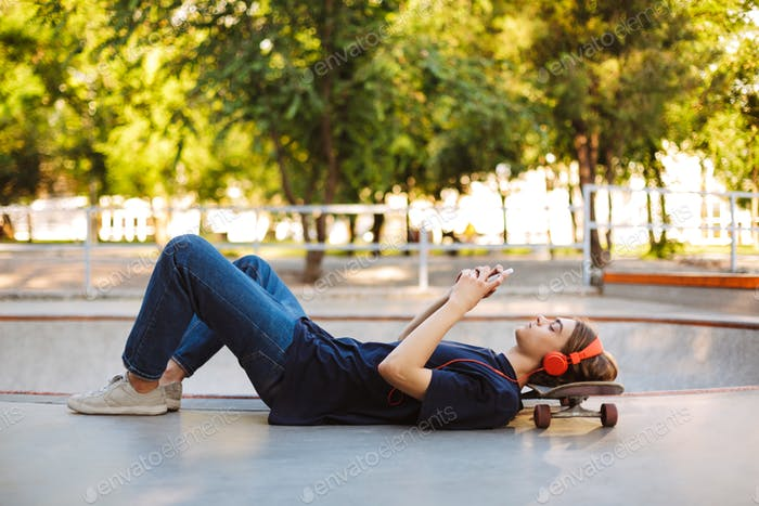 Young skater in orange headphones lying on skateboard thoughtful