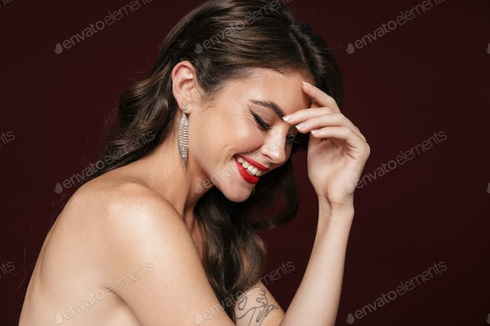 Image of joyful shirtless woman laughing and looking downward