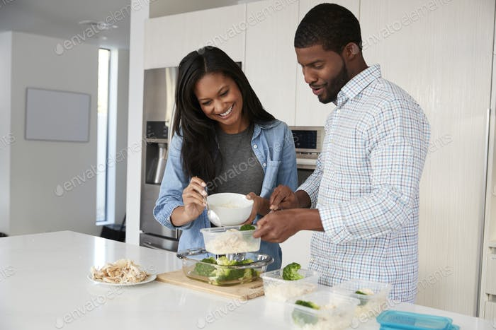 Couple In Kitchen Preparing High Protein Meal And Putting Portions Into Plastic Containers