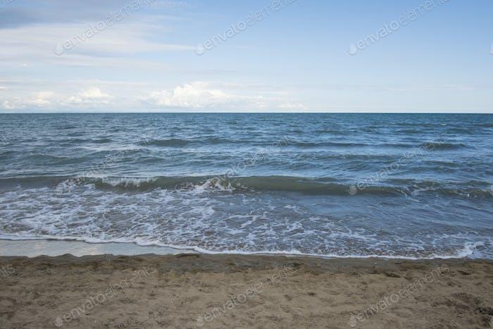 Sandy natural coastline and waves
