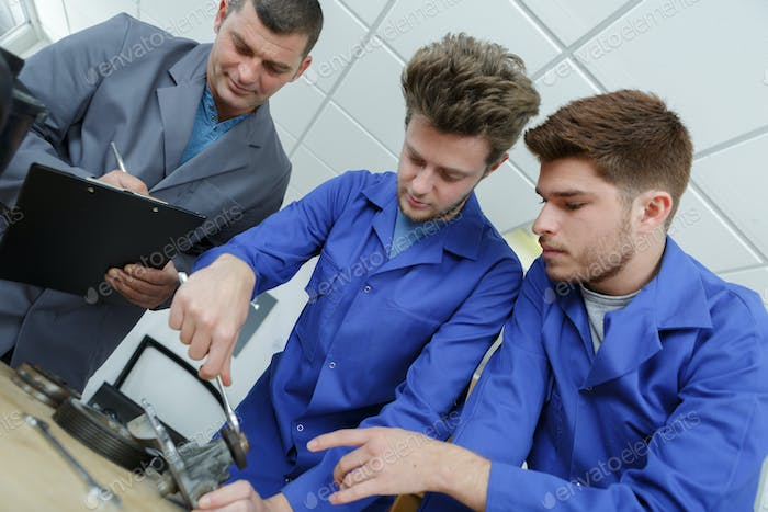 Tutor assessing two young male engineers