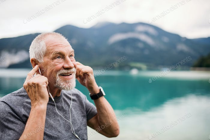 Senior man with earphones standing by lake in nature, listening to music.