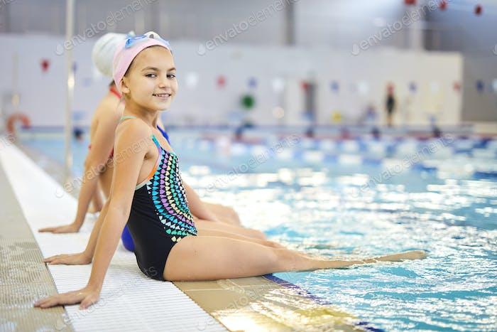 Little girl sitting near the pool