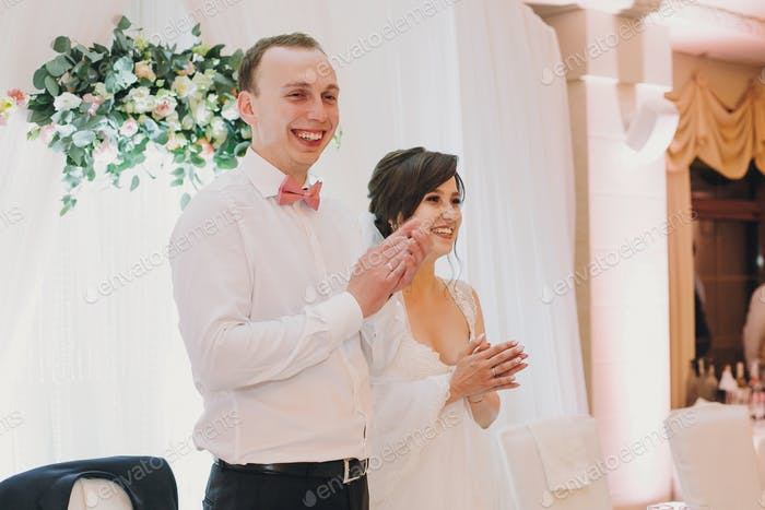 Gorgeous bride and stylish groom smiling and clapping hands