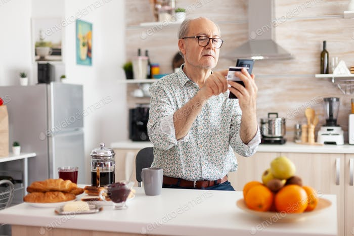 Pensioner paying online using credit card and application from smartphone
