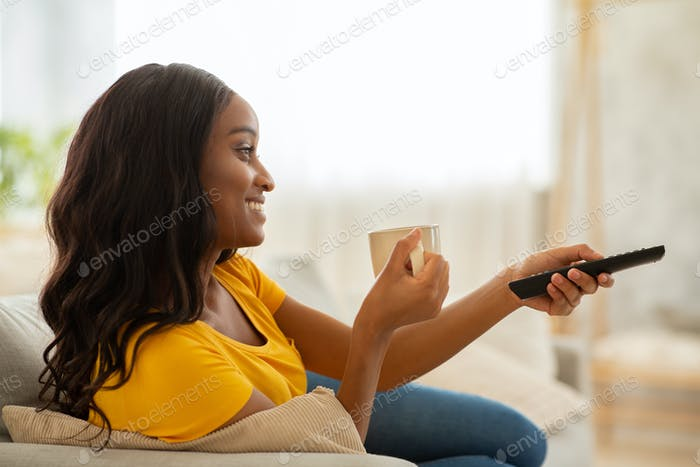 Side view of black lady with remote control and coffee watching TV at home
