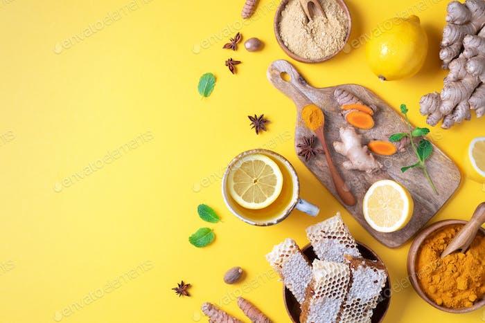 Würziges gesundes Kurkuma Getränk mit Zitrone, Ingwer, Honig auf gelbem Hintergrund. Immunsystem-Booster