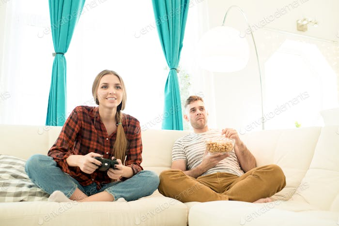 Excited girl playing video game while boyfriend eating popcorn