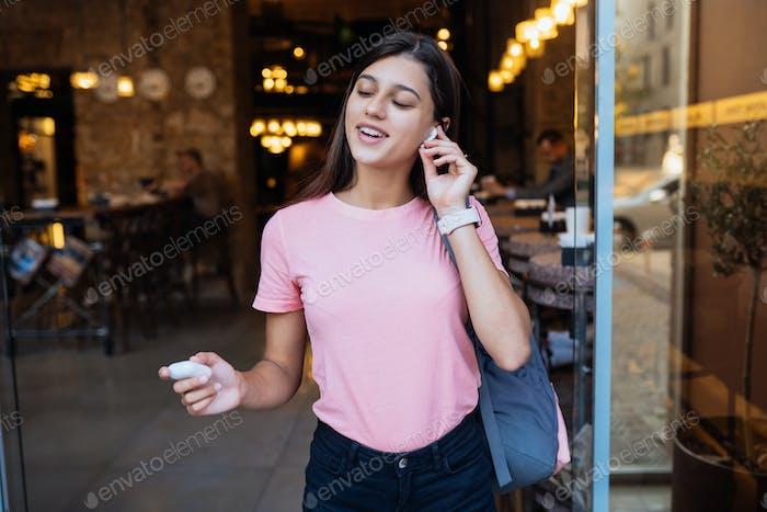 Красивая девушка с беспроводными наушниками