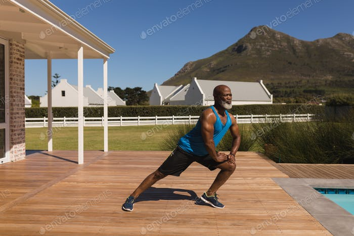 Active senior African American man performing stretching exercise