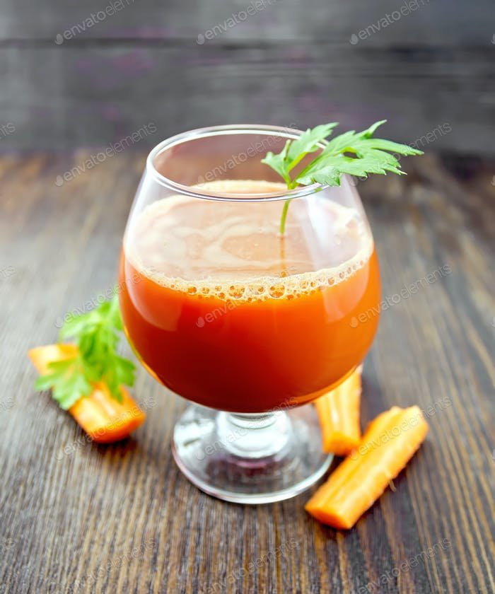 Juice carrot in wineglass on board
