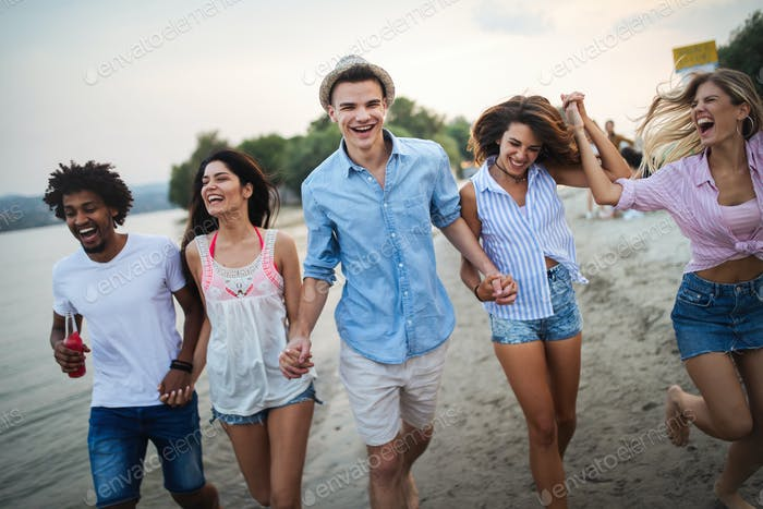 Group of friends having fun at the beach on a sunny day