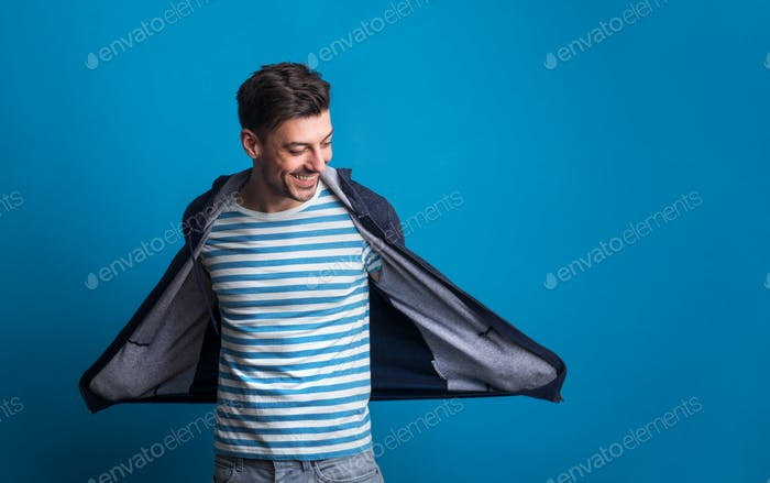 Portrait of a young happy man in a studio on a blue background.