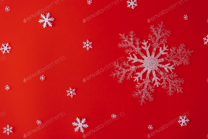 Red Christmas background with snowflakes. Flat lay New year minimal pattern.