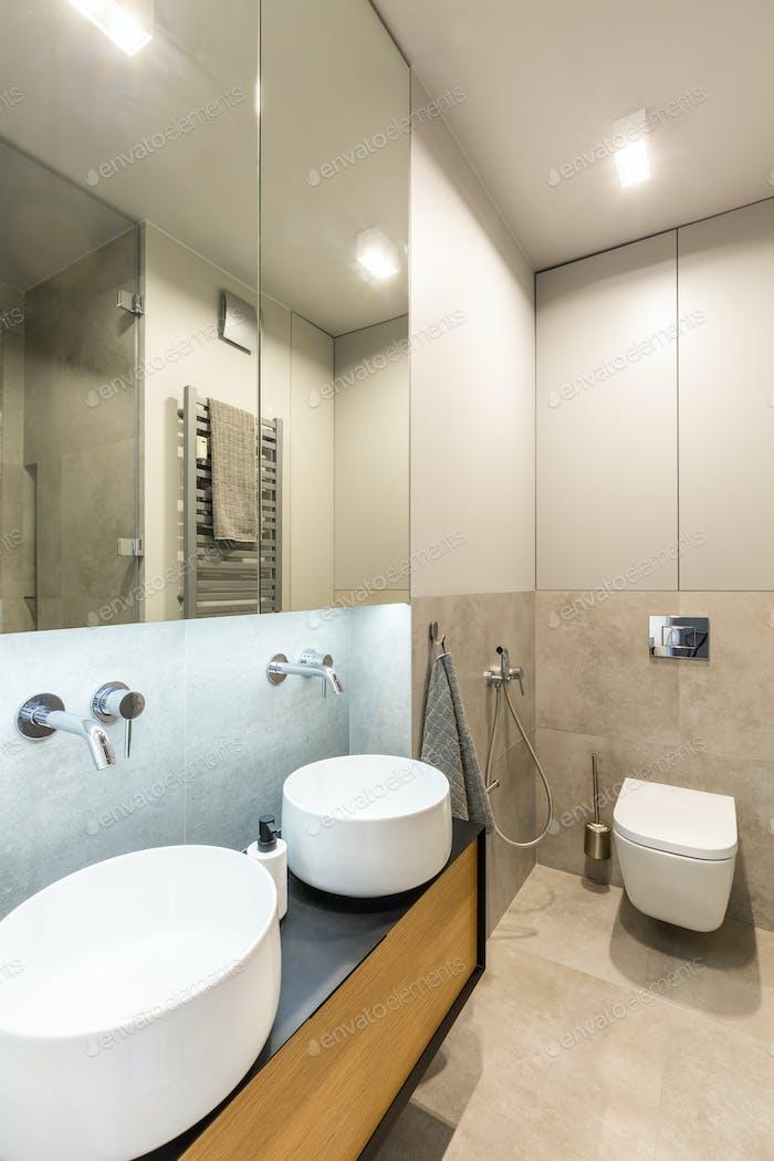 Mirror above white washbasins in beige bathroom interior with li