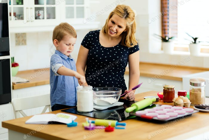 Child helping mother bake cookies