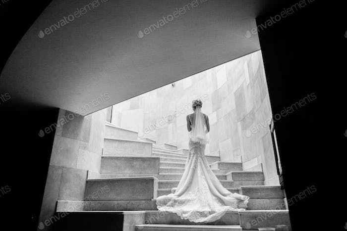 Stylish bride posing on stairs at hotel
