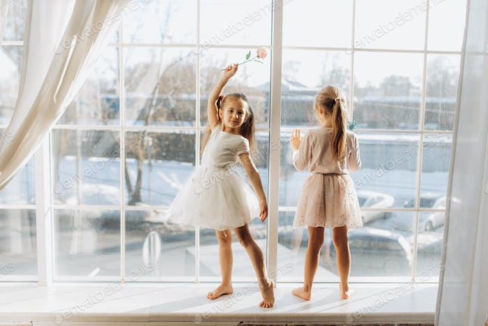 Two little sisters dressed in the beautiful dresses stand on the windowsill next to the mirror