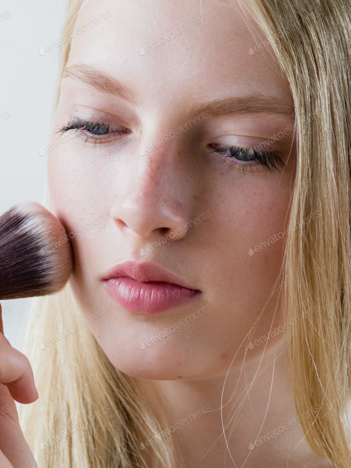 Makeup brush powder woman applying cosmetics natural portret