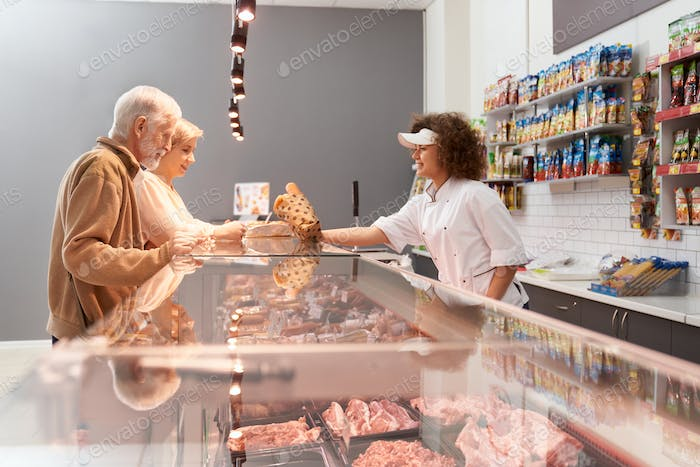 Female butcher giving eldery man with wife sausages