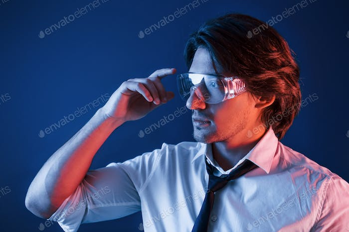 Beautiful man in glasses and in suit and tie is in the studio with blue neon lighting