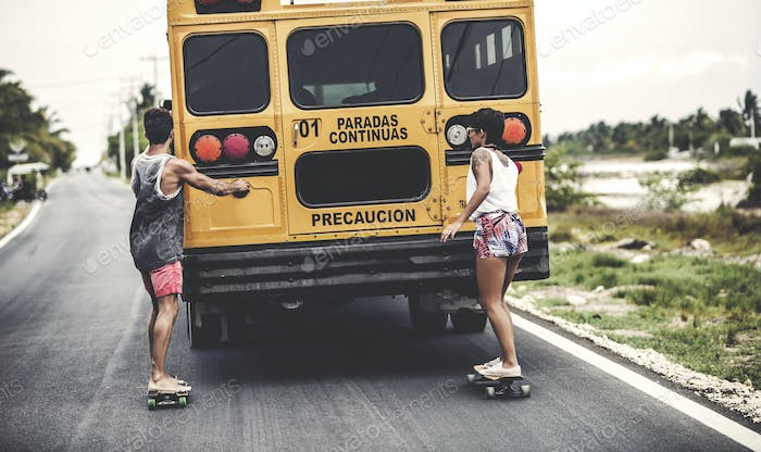 Two young people skateboarding while holding on to a moving school bus.