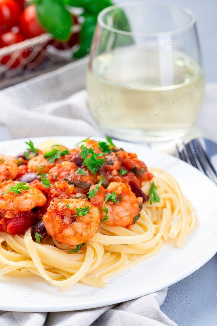 Italienisches Gericht Garnelen Linguine Puttanesca, Pasta mit Garnelen in würziger Tomaten-Basilikum-Sauce vertikal