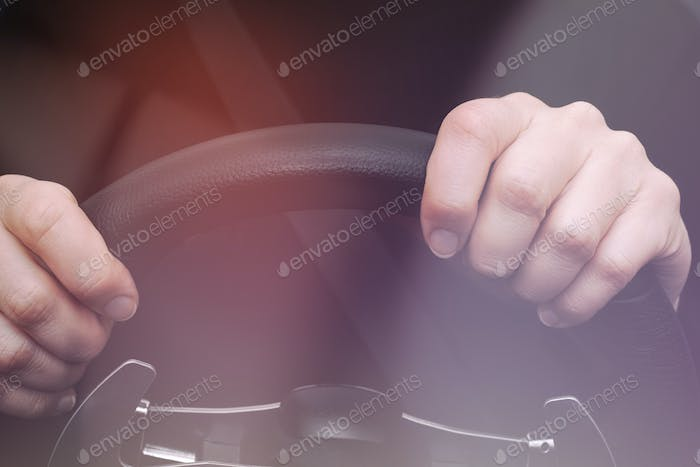 Woman's hands on steering wheel of a car