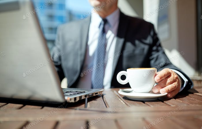 senior businessman with laptop and coffee outdoors