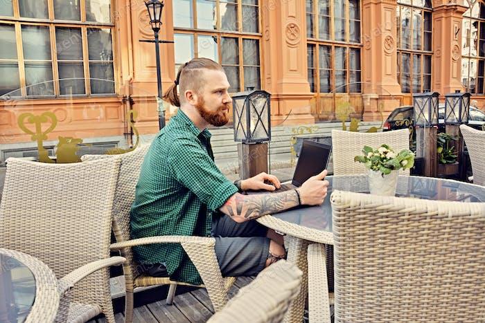 Татуированный мужчина с помощью ноутбука в открытом уличном кафе.
