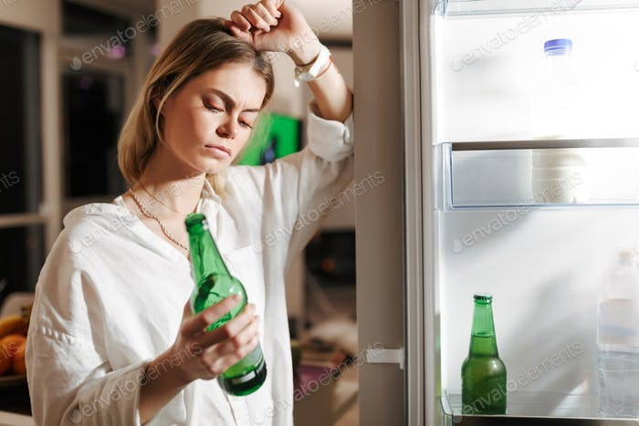 Young woman standing on kitchen at night near opened fridge thoughtfully looking on beer