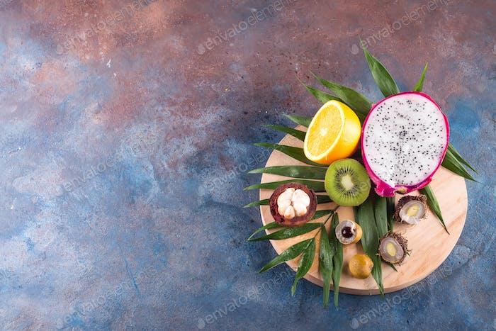 Tropische Halbfrüchte Sortiment auf einem hölzernen runden Spiel auf einem Steinhintergrund Muster. Draufsicht. Kopieren