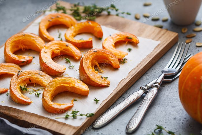 Thumbnail for Baked pumpkin slices with thyme on a wooden board over grey table. Seasonal food vegetarian recipe.