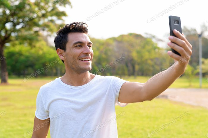 Happy young handsome Hispanic man taking selfie at the park