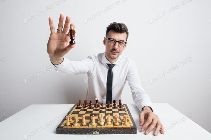 Portrait of a young man in a studio, playing chess and holding a king chessman.