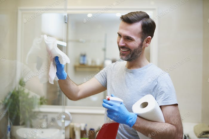 Happy man cleaning his home