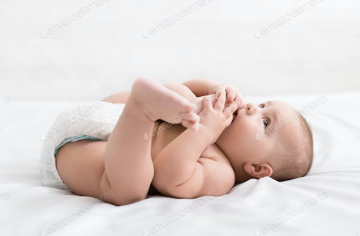 Adorable little baby sucking foot lying on bed