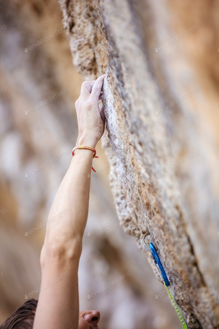 Cropped view of climber's hand on cliff