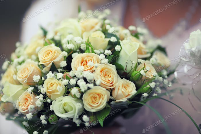 Round bouquet of small roses in hands of bride