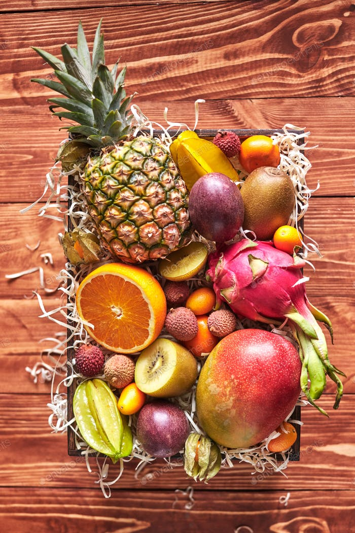 The box with exotic tropical fruits - fresh ripe pineapple, mango, dragon fruit, orange, carambola
