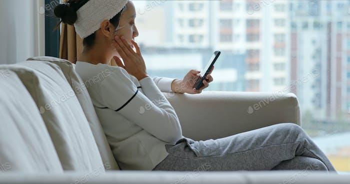 Mujer aplicar la máscara de papel y el uso del teléfono móvil