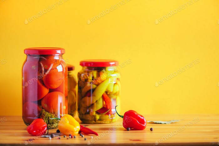 Preserved vegetables in glass jars on orange background. Copy space. Healthy fermented food concept