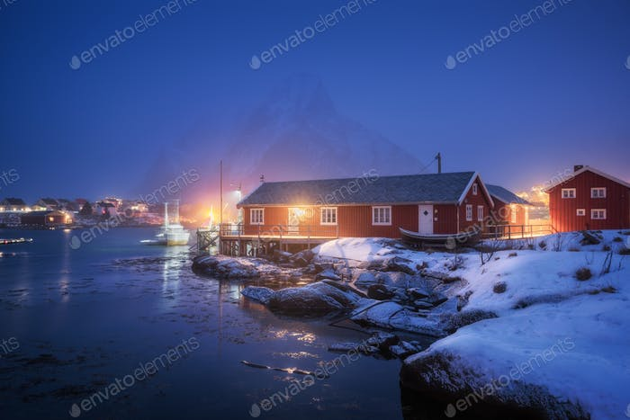 Beautiful norwegian Rorbu on sea cost and snowy mountain at night
