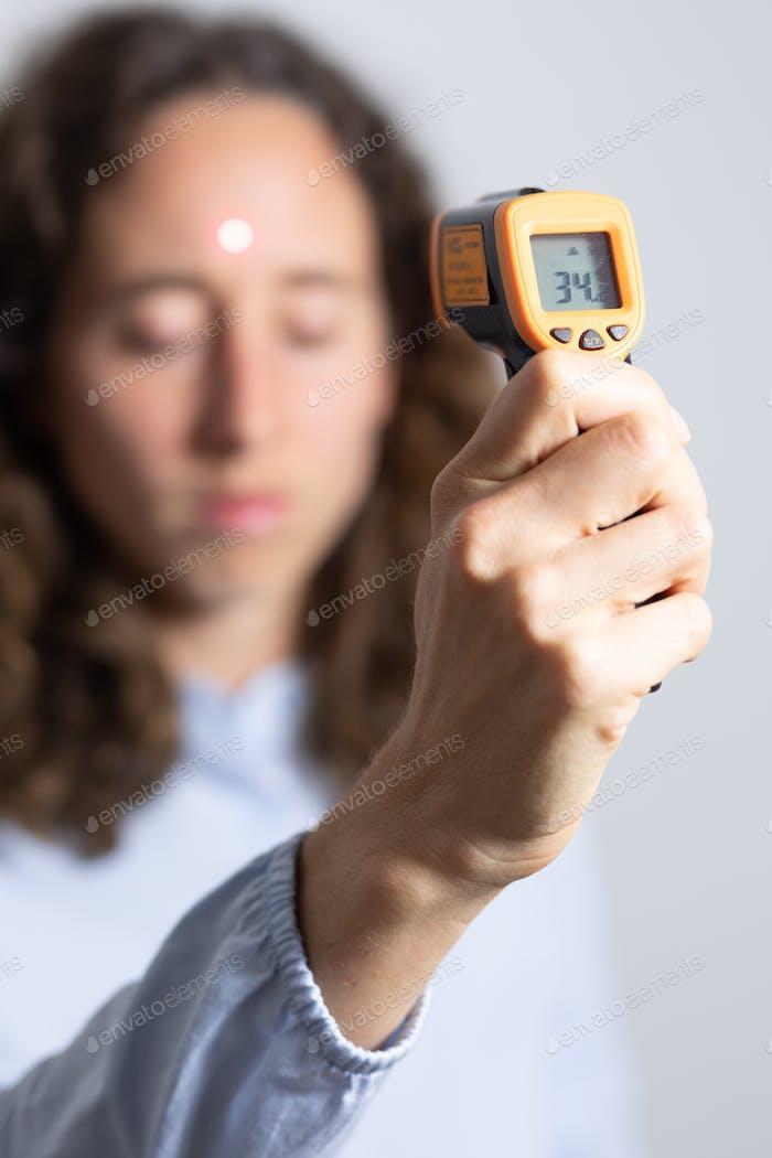 Caucasian woman using gun thermometer during coronavirus Covid19 pandemic